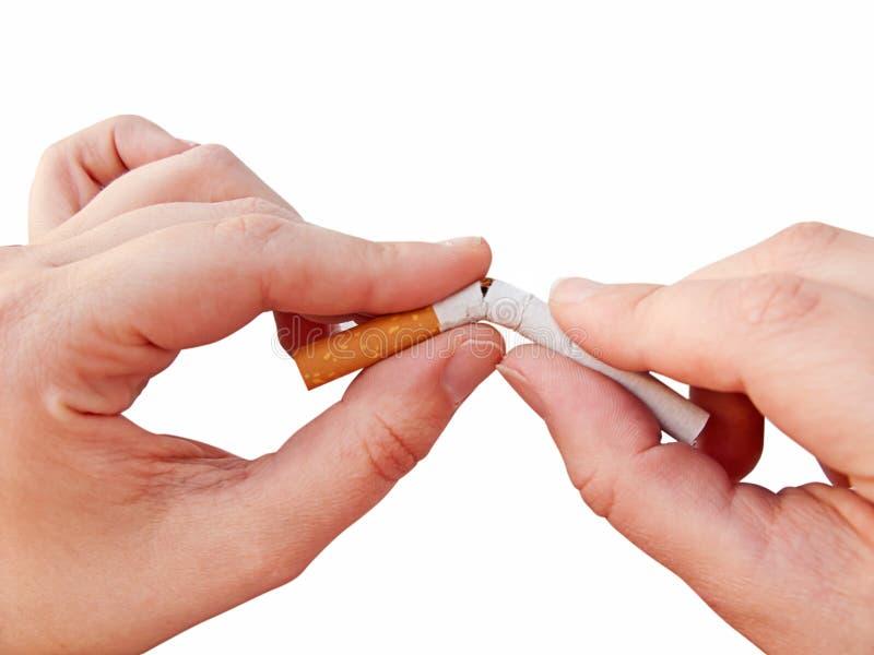 Mãos que quebram um cigarro imagens de stock royalty free