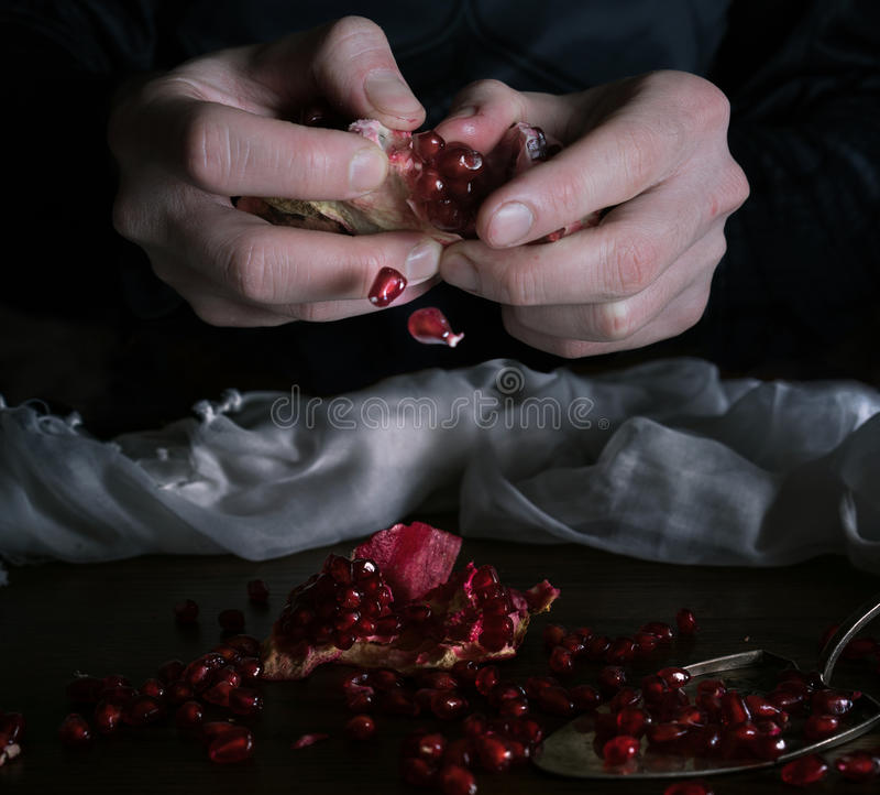 Mãos que recolhem sementes da romã para fazer o suco fotografia de stock