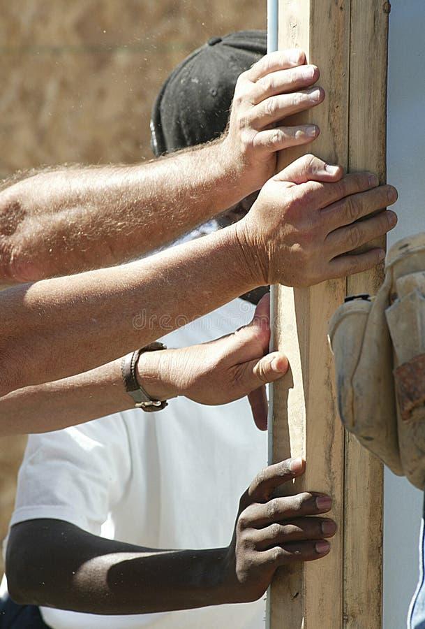 Mãos que suportam uma parede foto de stock