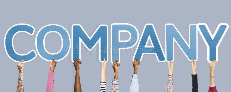 Mãos que sustentam as letras azuis que formam a empresa da palavra imagem de stock royalty free