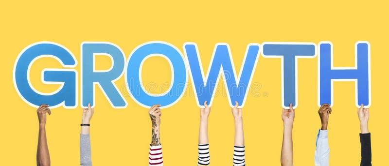 Mãos que sustentam as letras azuis que formam o crescimento da palavra foto de stock