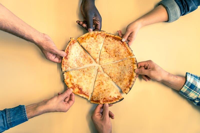Mãos que tomam fatias da pizza imagem de stock