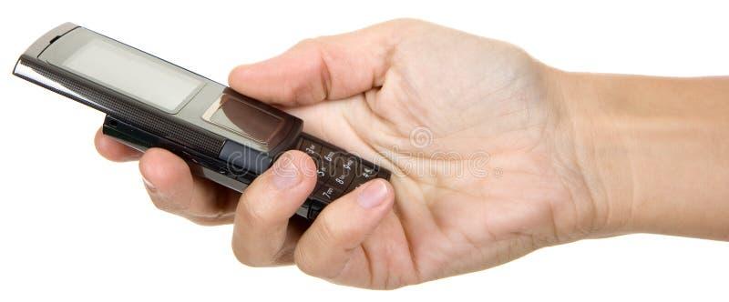 Mãos que trabalham em um telefone imagem de stock