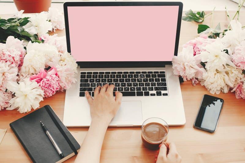 Mãos que trabalham no portátil à moda com as peônias vazias da tela, do copo de café, do caderno, do telefone, do rosa e as branc foto de stock