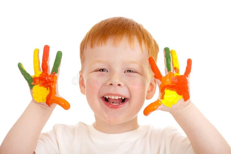 Mãos Red-haired da criança pintadas em cores brilhantes foto de stock