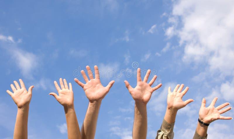 Mãos rised acima no ar através do céu fotos de stock