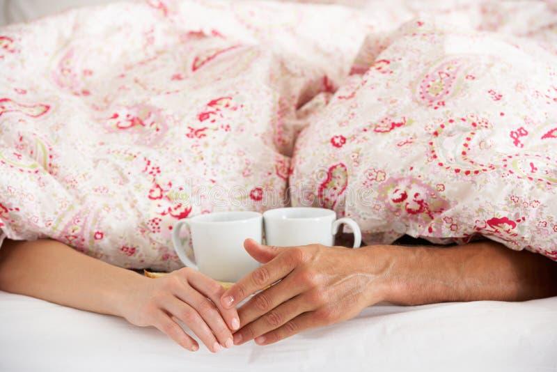 Mãos românticas da terra arrendada dos pares sob o Duvet na cama foto de stock