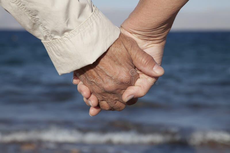 Mãos sênior da terra arrendada dos pares na praia foto de stock