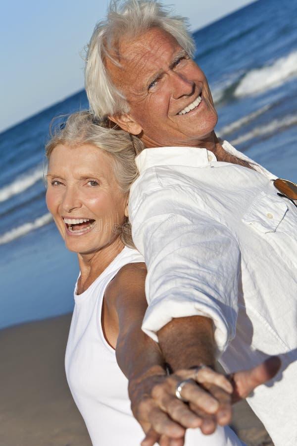 Mãos sênior felizes da terra arrendada dos pares na praia fotos de stock royalty free