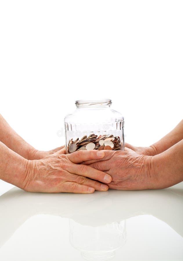 Mãos sênior que prendem um frasco com moedas fotografia de stock royalty free
