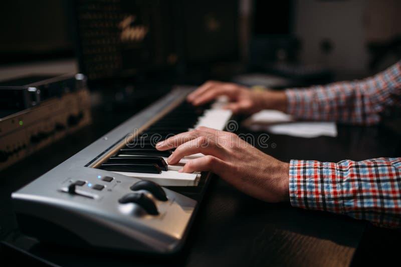 Mãos sadias masculinas do produtor no teclado musical imagens de stock