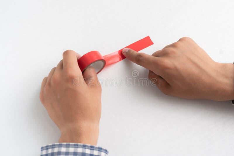 mãos segurando uma fita adesiva colorida e aplicando-a nas superfícies brancas foto de stock