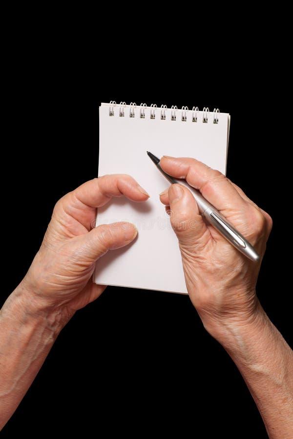 Mãos superiores da mulher com pena e o caderno vazio Writi da pessoa idosa imagem de stock royalty free