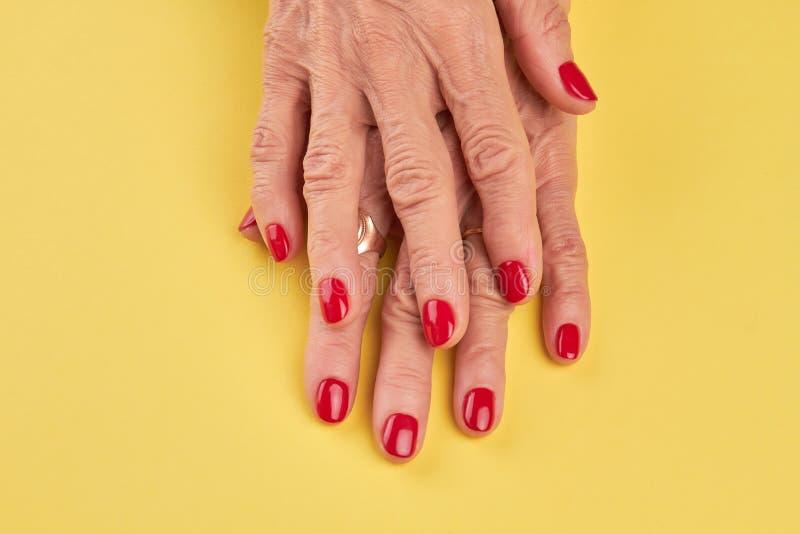 Mãos superiores da mulher com tratamento de mãos vermelho perfeito imagem de stock royalty free