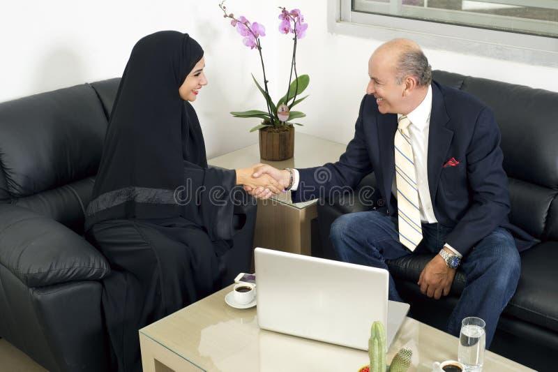 Mãos superiores de Shaking do homem de negócios com hijab vestindo da mulher foto de stock royalty free