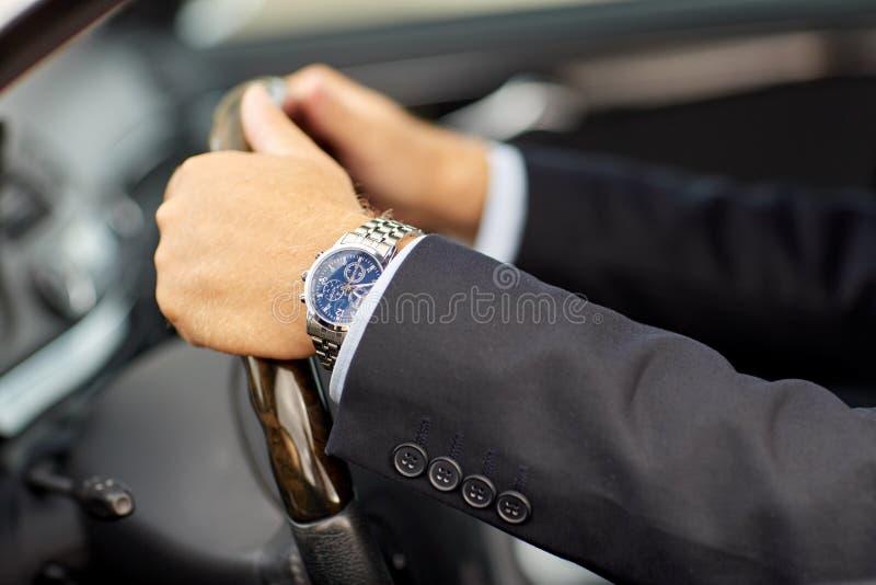 Mãos superiores do homem de negócios que conduzem o carro foto de stock