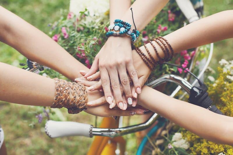 Mãos unidas das amigas close up, moças em braceletes do boho fotografia de stock