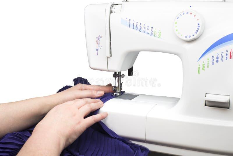 Mãos usando a máquina de costura foto de stock