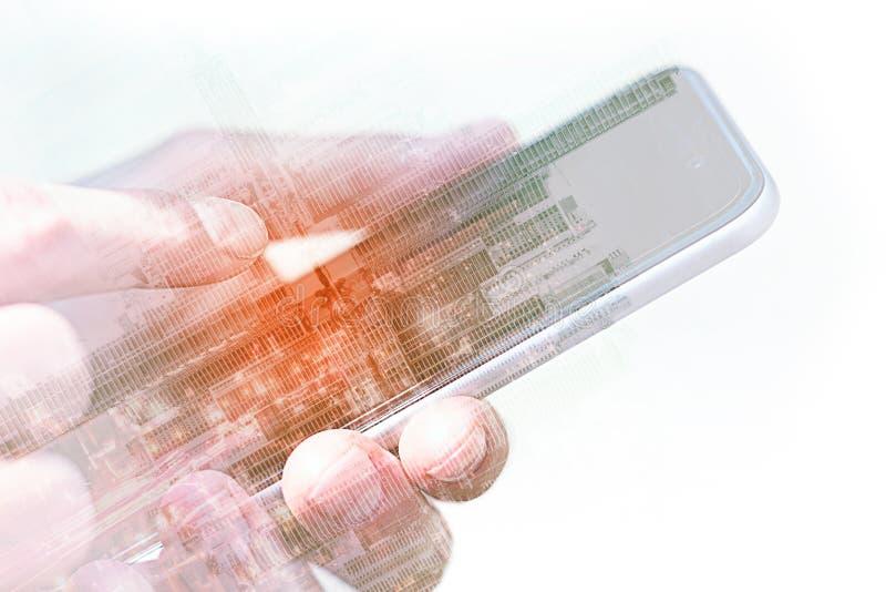 Mãos usando o close up do telefone celular/smartphone com exposição dobro da skyline da cidade imagem de stock royalty free