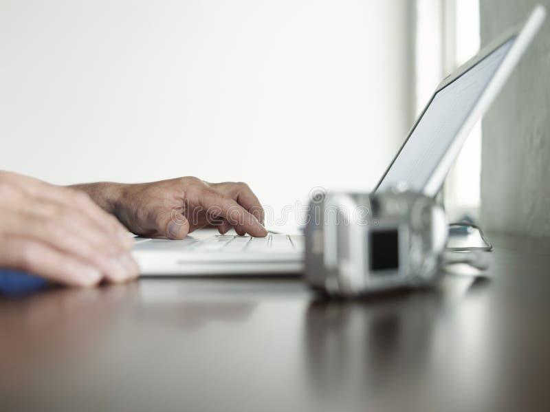 Mãos usando o escritório do portátil em casa fotos de stock royalty free