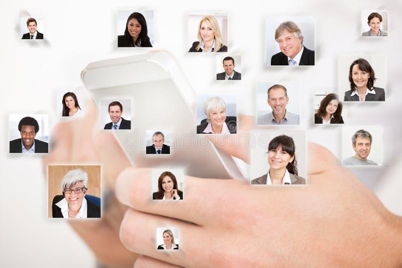 Mãos usando o telefone celular que representa uma comunicação global foto de stock royalty free