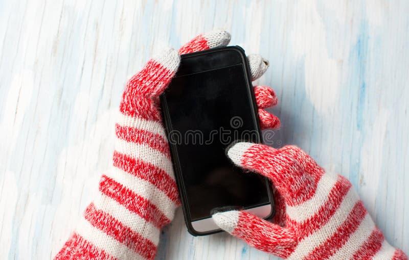 Mãos usando o telefone em luvas do inverno imagens de stock