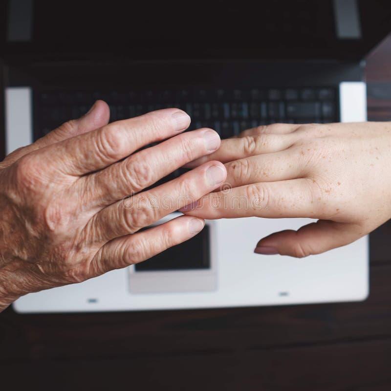Mãos velhas e das jovens mulheres no fundo do teclado imagens de stock royalty free