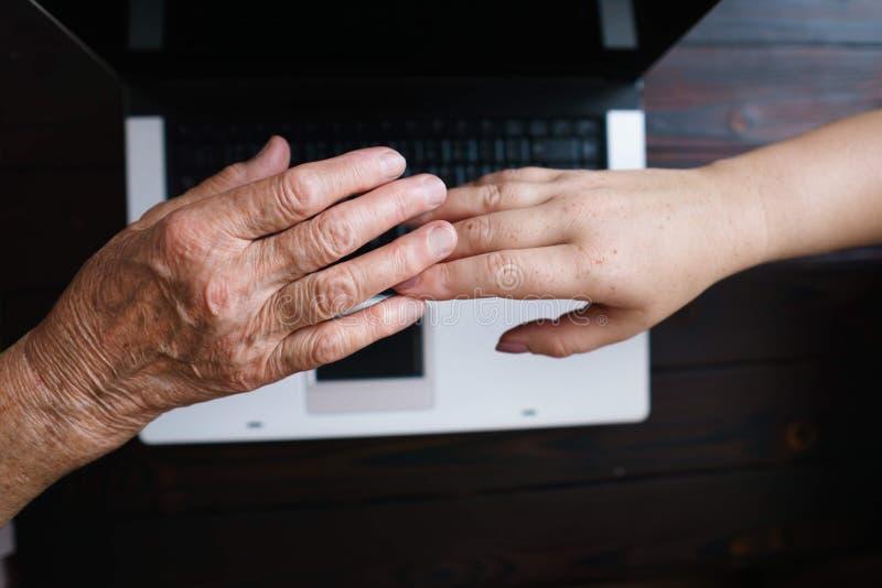 Mãos velhas e das jovens mulheres no fundo do teclado imagem de stock
