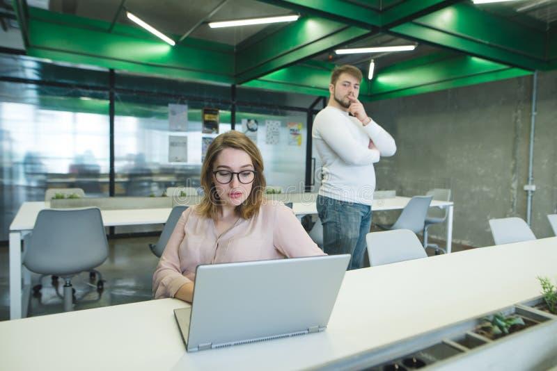 męża szef wzgardza dla kobiety która pracuje na laptopie w miejsce pracy Sytuacja w biurze obraz stock