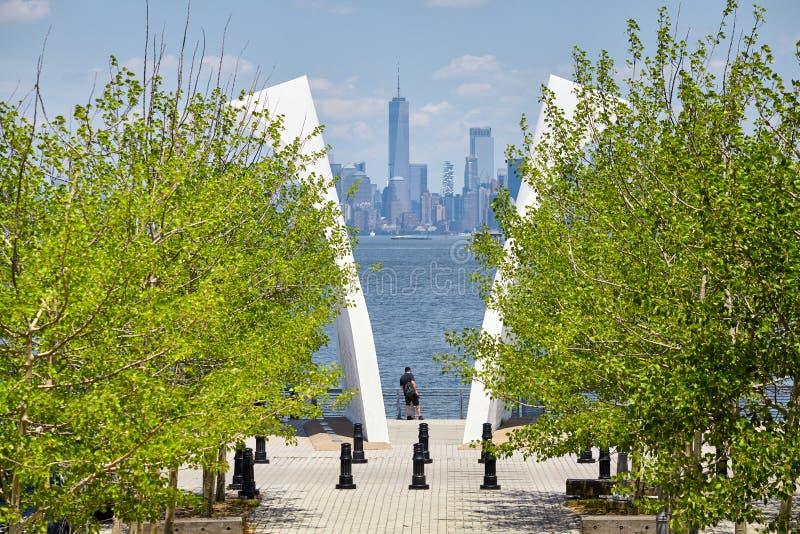 Mężczyzn stojaki między pocztówkami, Staten Island Wrzesień 11 pomnik z Manhattan w odległości zdjęcie stock