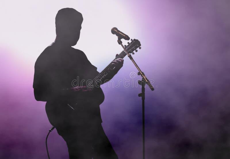 Mężczyzna bawić się gitarę pod światło reflektorów na scenie zdjęcie stock