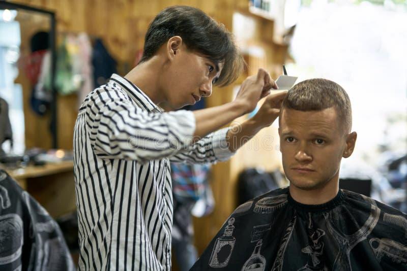 Mężczyzna ciie jego włosy w azjatykcim zakładzie fryzjerskim obraz stock