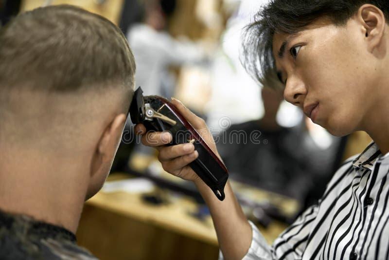 Mężczyzna ciie jego włosy w azjatykcim zakładzie fryzjerskim zdjęcia royalty free