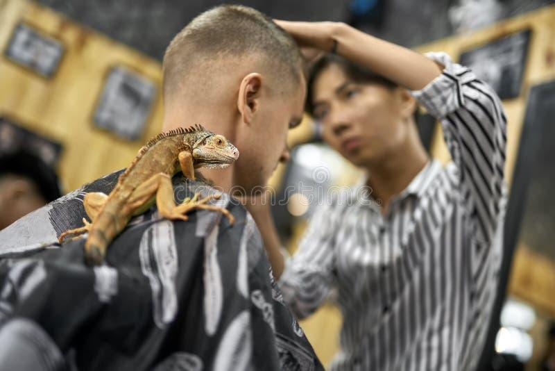 Mężczyzna ciie jego włosy w azjatykcim zakładzie fryzjerskim fotografia stock