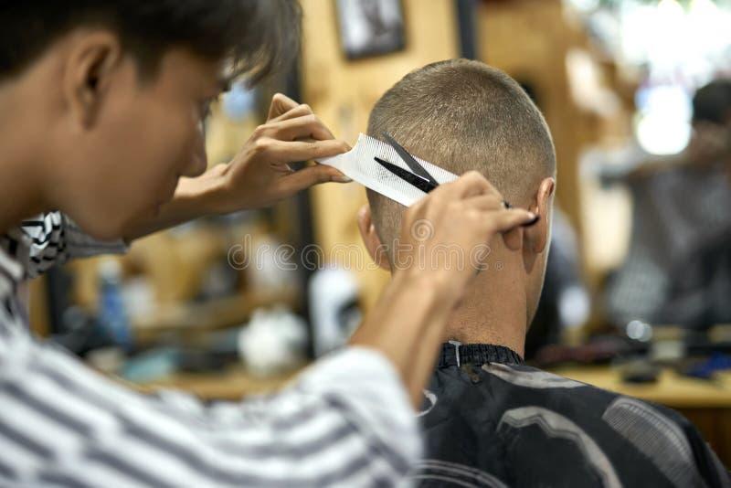 Mężczyzna ciie jego włosy w azjatykcim zakładzie fryzjerskim obrazy stock