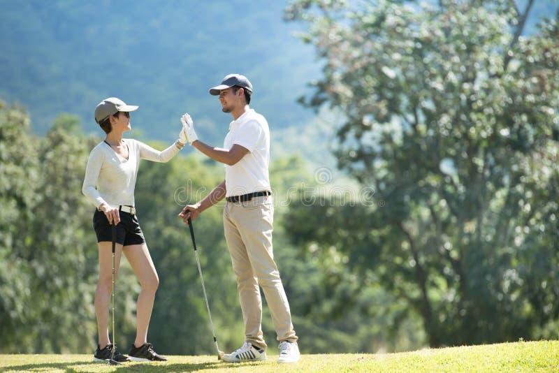 Mężczyzna i kobieta bawić się golfa na pięknym naturalnym polu golfowym zdjęcia stock
