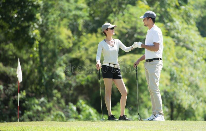 Mężczyzna i kobieta bawić się golfa na pięknym naturalnym polu golfowym obrazy stock
