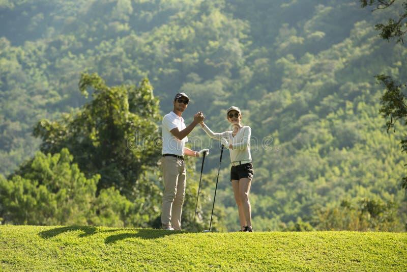 Mężczyzna i kobieta bawić się golfa na pięknym naturalnym polu golfowym fotografia royalty free