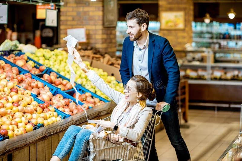 Mężczyzna i kobieta ma zabawę podczas zakupy w supermarkecie fotografia stock