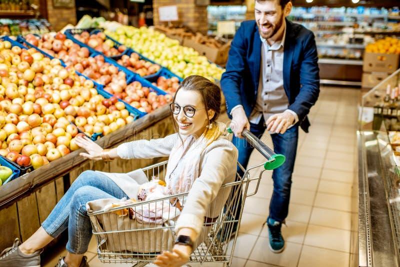 Mężczyzna i kobieta ma zabawę podczas zakupy w supermarkecie zdjęcie stock