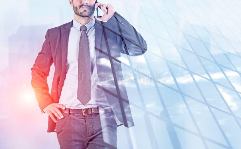 Mężczyzna opowiada na telefonie blisko drapacz chmur zdjęcia stock