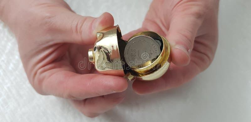 Mężczyzna otwiera małego złotego prosiątko banka folującego z pięć sheckel monetami obraz stock