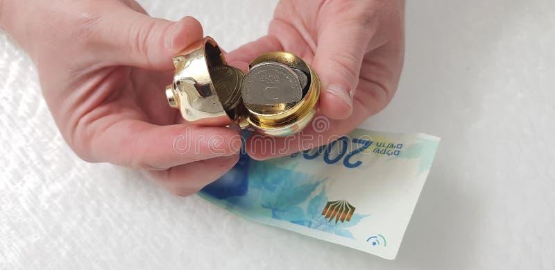 Mężczyzna otwiera małego złotego prosiątko banka folującego z pięć sheckel monetami zdjęcia stock