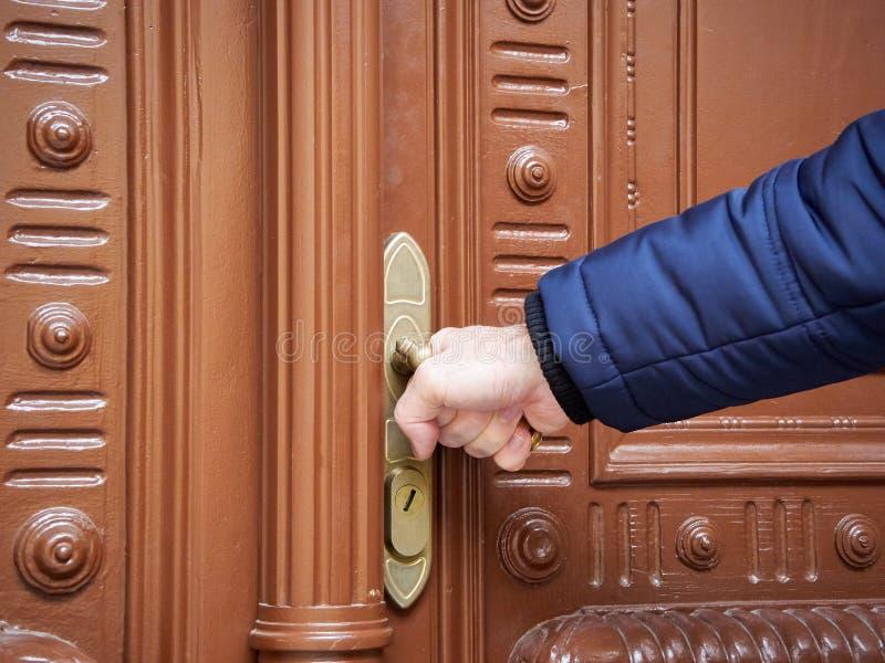 Mężczyzna otwiera zamkniętego starego drzwi Stara rękojeść i ręka w zimy kurtce zdjęcie royalty free