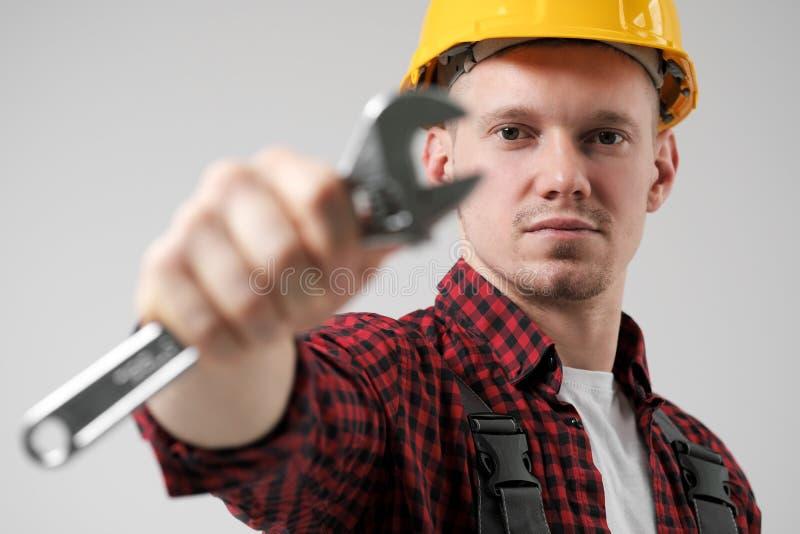 Mężczyzna, pracownik w żółtym hełmie w, pracujący kombinezony i czerwona w kratkę koszula, trzymamy stal nastawcza zdjęcia stock