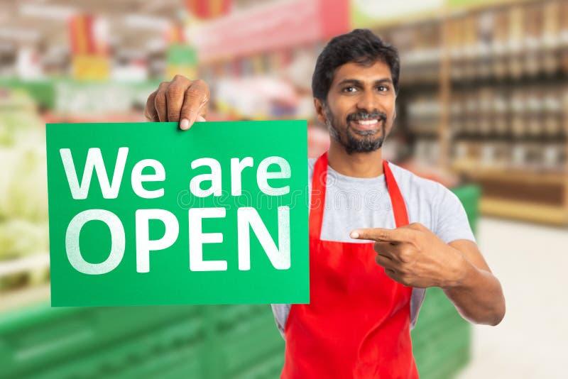 Mężczyzna pracuje przy hypermarket wskazuje przy jesteśmy otwartym papierem fotografia stock