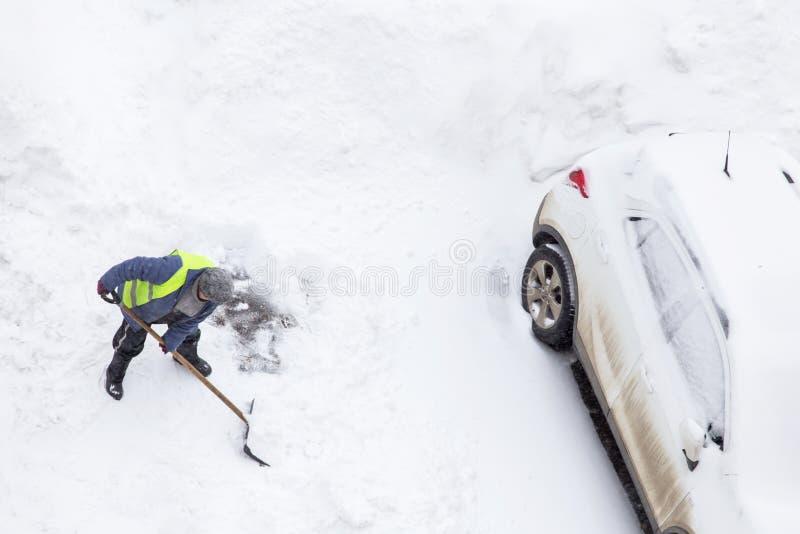 Mężczyzna przeszuflowywa śnieżnego pobliskiego samochód na parking Odgórny widok obraz royalty free