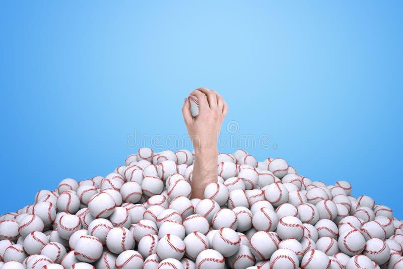 Mężczyzna ręka trzyma baseballa, wyłania się spod dużego stosu baseballe obraz stock