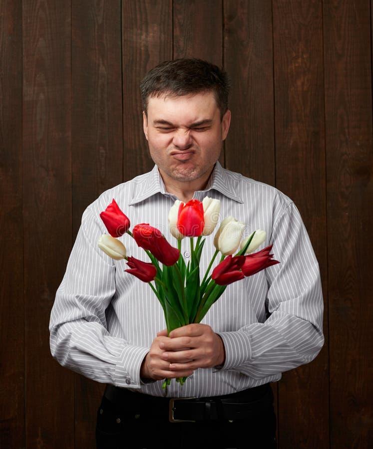 Mężczyzna trzyma czerwonego kwiatu bukiet z okropnym odorem fotografia royalty free