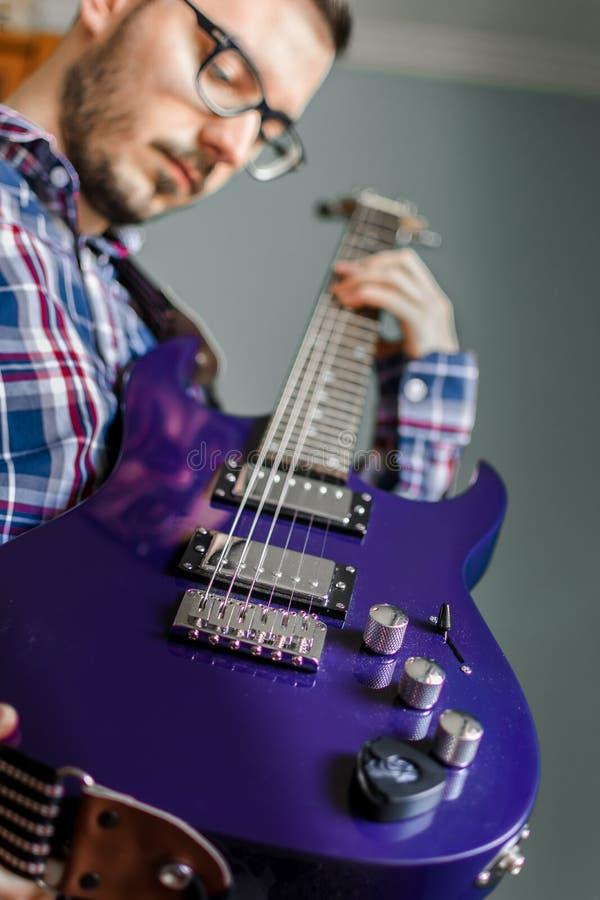 Mężczyzna uczy się bawić się gitarę elektryczną w domu zdjęcia royalty free